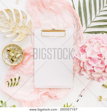 Modern Home Office Desk Workspace With Blank Paper Clipboard, Pink Hydrangea Flowers Bouquet, Tropic