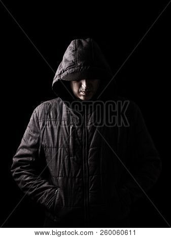 Scary and creepy caucasian or white man hiding in the shadows, with the face and identity hidden with the hood, and standing in the darkness. Low key, black background. Concept for fear, mystery