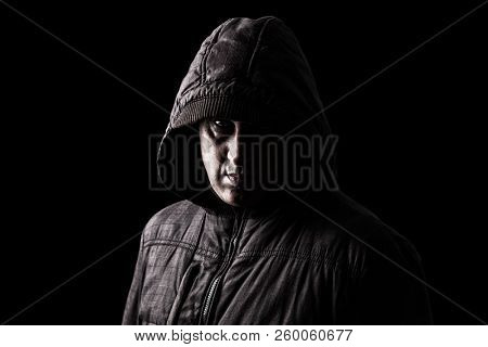 Scary Caucasian or white mature man hiding in the shadows, with the face partly hidden with the hood, and standing in the darkness. Black background. Concept for stalker, fear, danger, crime.