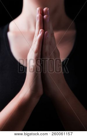 Low key, close up of hands of a faithful woman praying, with hands folded and palms together in worship to god, on a black background. Concept for religion, faith, prayer and spirituality.