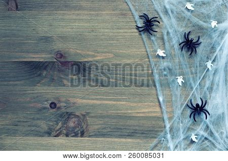 Halloween background in dark tones with spider web, spiders and ghosts as symbols of Halloween on the wooden background. Halloween holiday concept