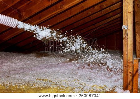 Worker Spraying Mineral Rock Wool Of Thermal Insulation Layer Under The Roof House Attic Insulation