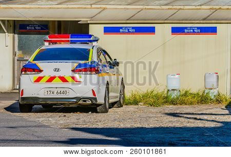 Seoul,south Korea; September 9,2018: Unoccupied Police Car Parked In Gravel Parking Lot In Front Of
