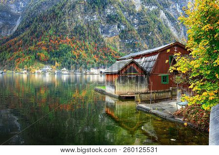 Sunny Autumnal Day At Famous Hallstatt Lakeside Town Reflecting In Hallstattersee Lake. Location: Re
