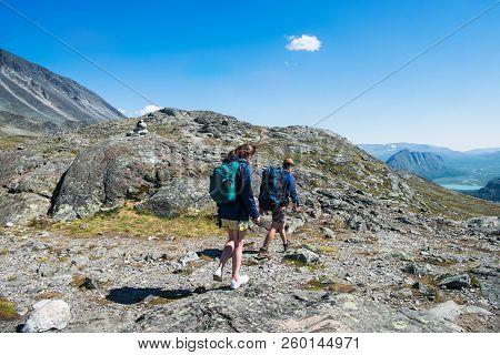 Couple Of Hikers Walking On Besseggen Ridge In Jotunheimen National Park, Norway