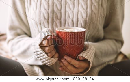 Women's Hands In Sweater Are Holding Cup Of Hot Coffee, Chocolate Or Tea. Concept Winter Comfort, Mo