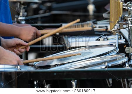 the flashing drumsticks of a sideline percussionist at marching band rehearsal poster