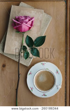 Coffee in a vintage teacup with a faded pink rose