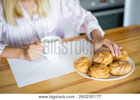 Close Up Of Woman In Pajamas Drinking Coffee With Pastry In The Kitchen