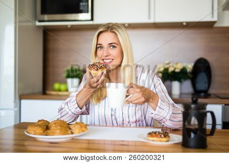 Portrait Of Young Woman In Pajamas Eating Donuts And Drinking Coffee In Modern Kitchen