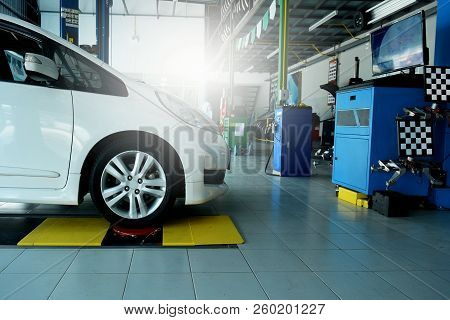 The White Car Awaiting On Position During Wheel Alignment At The Car Repair Shop