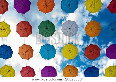 Multicolored Umbrellas Hanging High Above The Ground Against A Blue Sky With White Clouds