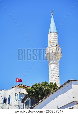 Minaret Of Kelerlik Mahallesi Cami Mosque With The Official Flag Of The Republic Of Turkey Waving In