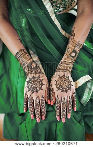 Close-up Shot Of Indian Bride Back Hand With Mehndi (henna Tattoo) With Beautiful Sari In Green Lehe
