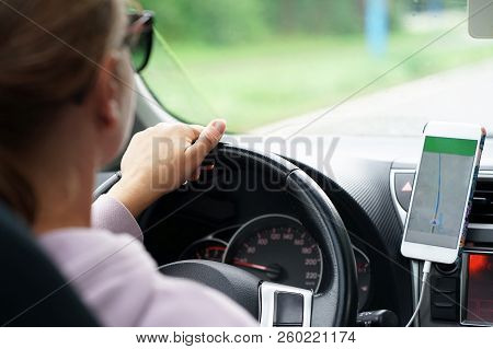 Hands Of A Woman With A Steering Wheel, Driving A Car On A Smartphone Navigator. Photo Of A Young Wo