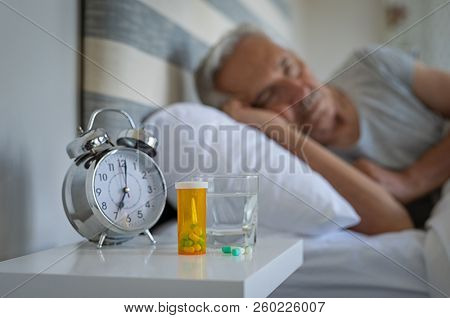 Medical pills and alarm clock with senior man sleeping in background. Silver alarm clock and medicines on table while man resting on bed. Bottle of capsules with glass of water kept on night table.