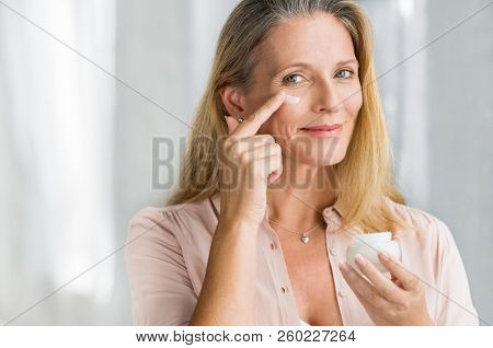 Smiling senior woman applying anti-aging lotion to remove dark circles under eyes. Happy mature woman using cosmetic cream to hide wrinkles below eyes. Lady using day moisturizer.