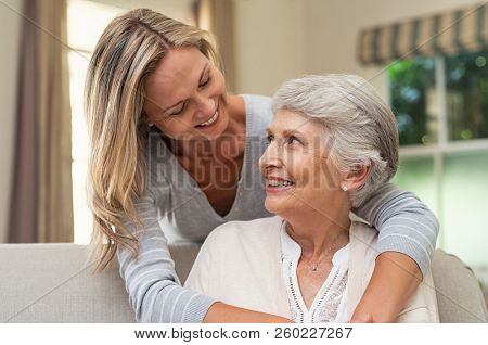 Portrait of old mother and mature daughter hugging at home. Happy senior mother and adult daughter embracing with love on sofa. Cheerful woman hugging from behind older mom and looking at each other.
