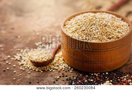 Quinoa White grains in a wooden bowl and spoon. Gluten free Healthy food. Diett, dieting concept. Seeds of white, red and black quinoa - Chenopodium quinoa