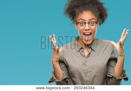 Young afro american woman wearing glasses over isolated background celebrating crazy and amazed for success with arms raised and open eyes screaming excited. Winner concept