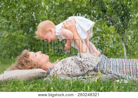 Little Princess Playing Outdoor. Baby Girl On Mother's Hands. Smiling Toddler With Mother. Life Begi