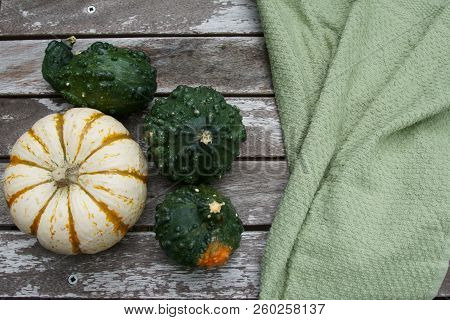 Colored Pumpkins For Fall Background With Copy Space And A Green Cloth