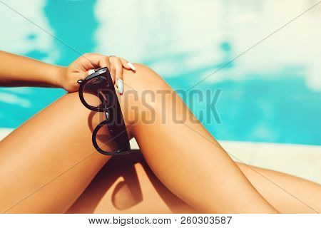 Sunglasses, Women's Legs Resting In Swimming Pool Background. Summer Holiday Traveling Concept Desig