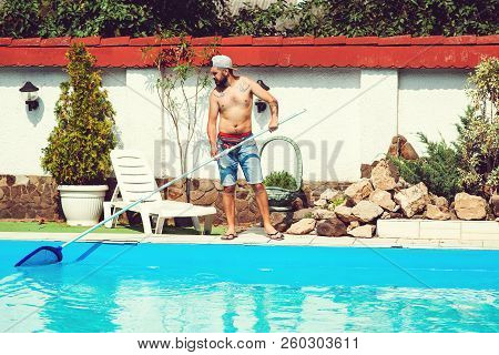 Swimming-pool Service Man Cleaning Water. Bearded Man Cleaning Swimming-pool In Private Villa. Clean
