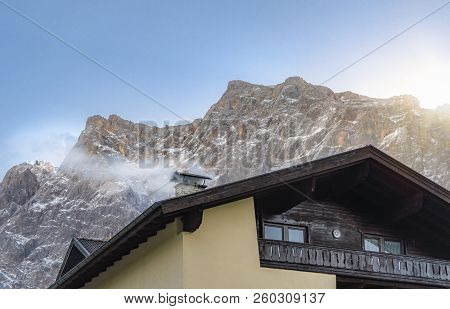 Cozy Winter Scene With The Rooftop Of A House, A Smoky Chimney, And The Snow-capped Alps Mountains,