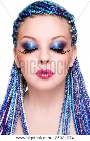 Portrait of young beautiful girl with fancy blue hairstyle and extra long fake eyelashes, on white background