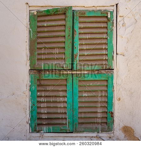 Old Grunge Window With Closed Green Shutters On Dirty Bricks Stone Wall, Cairo, Egypt