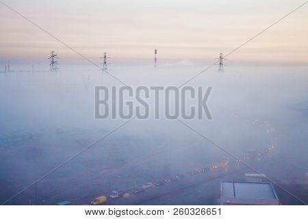 Morning Fog Covers The Factory And Electrotowers. Unusual Landscape. Cars In Fog