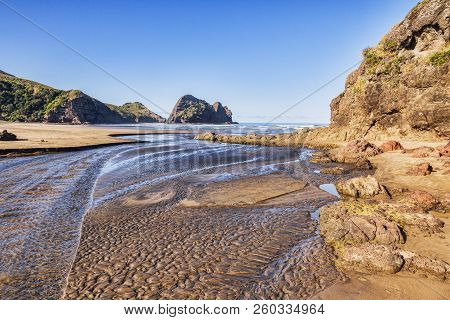 Piha Beach At Low Tide, With Deeply Textured Sand In The Stream Bed.