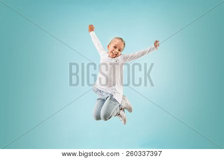 Adorable Small Child At Blue Studio. The Girl Is Jumping And Smiling. Young Emotional Surprised Teen