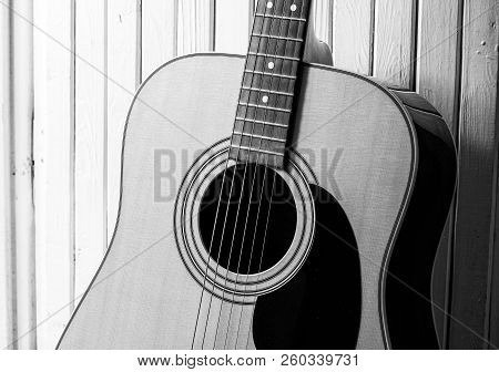 Acoustic Guitar On A Wooden Background. Close-up.