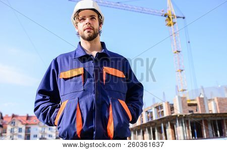 Guy In Protective Helmet Stand In Front Of Building And Crane. Control Construction Process. Builder