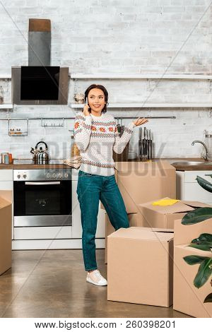Attractive Young Woman Talking On Smartphone And Doing Shrug Gesture During Relocation In New Home
