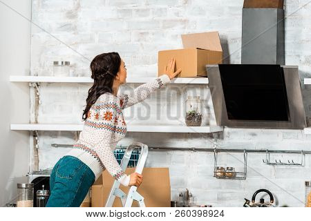 Rear View Of Woman Putting Cardbord Box On Shelf In Kitchen During Relocation At New Home