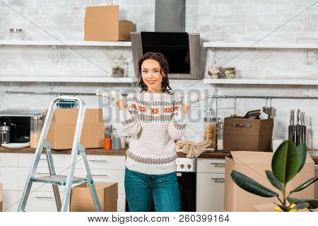 Beautiful Young Woman In Working Gloves Doing Shrug Gesture Near Ladder In Kitchen During Relocation