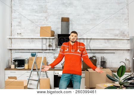 Young Man Doing Shrug Gesture In Kitchen With Cardboard Boxes During Relocation In New Home