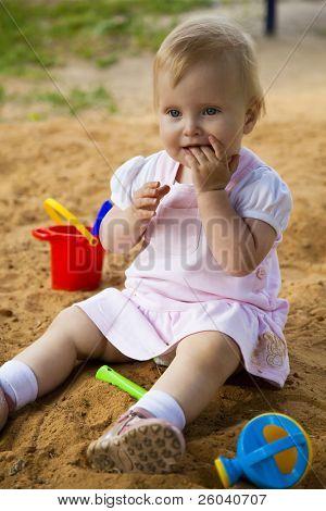 The little girl is sitting in sandbox