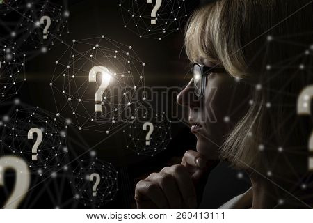Businesswoman Thinking Over Questions Arising On A Dark Background.