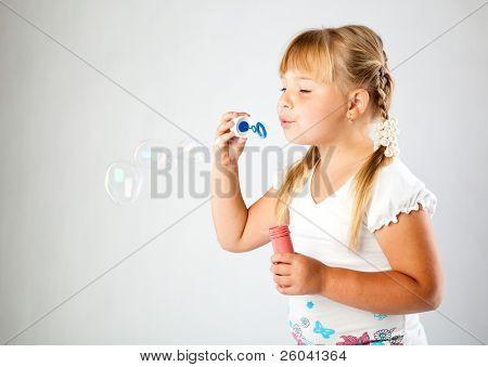 Blow menina bolhas de sabão em fundo cinza
