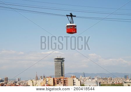 BARCELONA, SPAIN - APRIL 19, 2018: A vintage red cable car of the Transbordador Aeri Del Port crosses over the harbour towards Montjuic hill. The attraction first opened in 1929.