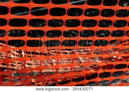 Vivid Orange Construction Safety Net With A Railroad Rail In The Background