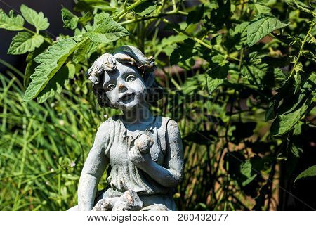 Stone Garden Statue Placed In A Tomato Patch In Direct Sunlight