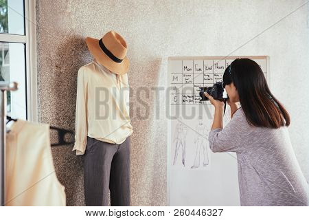 Fashion Designer Photographing Clothes On Mannequin For Her Blog