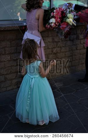 A Little Girl In A Gown Wants To Take Fiowers From Her Parents