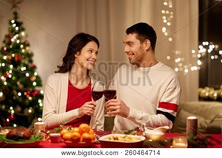 holidays, family and celebration concept - happy couple having christmas dinner at home and drinking red wine and clinking glasses