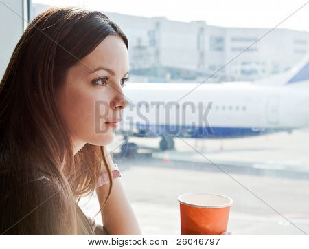 Young woman is drinking coffee in airport